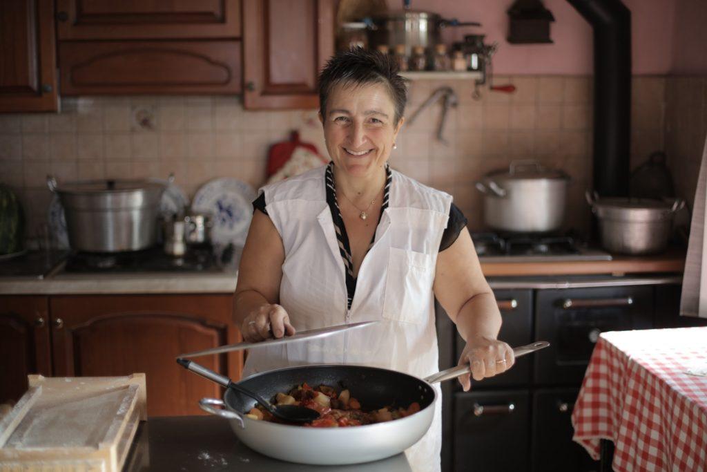 donna anziana che sorride mentre cucina