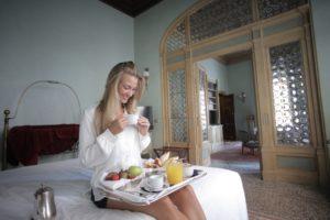 una giovane donna si gusta la sua colazione a letto