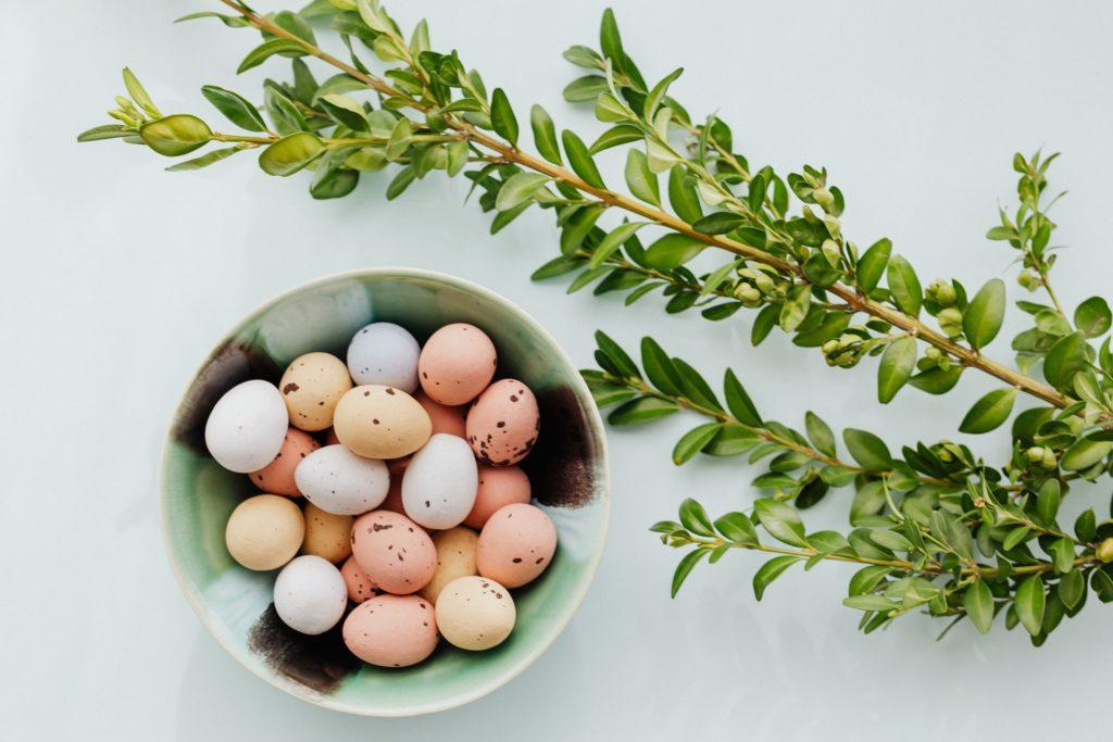 uova di pasqua dentro ad una ciotola con un ramoscello di ulivo